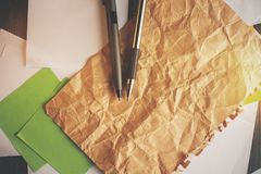 Crumpled paper sheet. Close up of crumpled paper sheet on office desk with other supplies. Mock up stock photos