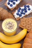 Crunchy cereal breakfast, banana smoothie. Close-up crunchy breads covered by ricotta cheese with blueberries royalty free stock photography