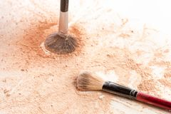 Close-up of crushed mineral shimmer powder golden color with makeup brush royalty free stock photography