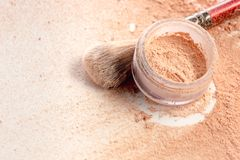 Close-up of crushed mineral shimmer powder golden color with makeup brush. On white background royalty free stock photos