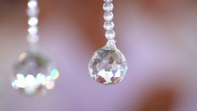 Close up Crystal ball from  Chandelier with blur Brown Pink background.