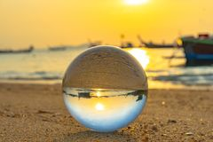 Close up crystal glass ball put on the beach. Crystal glass ball on the sandclose up crystal glass ball put on the beach in the morning stock photo