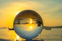 Close up crystal glass ball put on the beach. Crystal glass ball sphere reveals sunrise seascape with spherical perspective on the beach in Phuket island royalty free stock photography