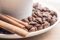 Close up of a cup of coffee with cinnamon and beans Royalty Free Stock Photos