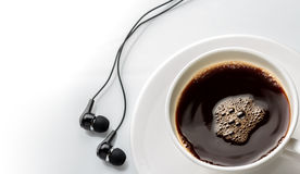 Close up cup of coffee with earphone on white . Royalty Free Stock Photo