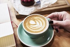 Close-up cup of coffee latte on wooden table in woman hands from above. Having lunch in cafe Royalty Free Stock Images