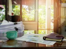 Close up of a cup of coffee and office supplies on desk. In office at morning, warm tone Royalty Free Stock Photography