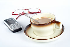 Close-up of a cup of coffee with the spoon inside, cellular phone and pair of glasses Royalty Free Stock Image