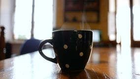 Close up of cup with coffee and steam on table. Close up footage of cup with coffee and steam on wood table of the kitchen stock video footage