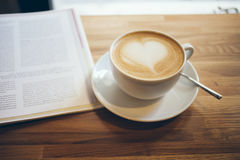 Close-up of cup of coffee on the wooden table. Morning, drinking coffee and readying newspaper. Coffee made with love Royalty Free Stock Photography