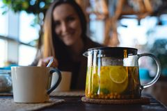 Close-up of a Cup and a glass teapot with sea buckthorn tea with lemon and herbs, on the background of a smiling girl royalty free stock image