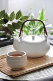 Close up a Cup of Hot Tea on Bamboo Mat. Close up a cup of hot tea with tea pot on bamboo mat stock photography