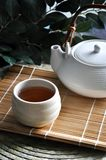 Close up a Cup of Japanese Hot Tea. With tea pot on bamboo mat royalty free stock image
