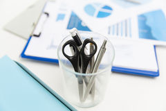 Close up of cup with scissors and pens at office Stock Images