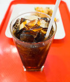 Close up of a cup of soft drink on the red tray with blurry food dish background Stock Photography