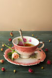 Close up of a cup of tea with roses on wooden table Royalty Free Stock Images