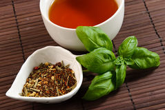 Close up of cup of tea with tea leaves. And basil leaves on a bamboo mat Royalty Free Stock Images