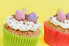 Cupcakes with chocolate eggs on yellow background Stock Photos