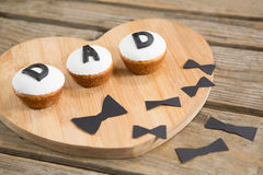 Close up of cupcakes with dad text by bow tie. On wooden table Stock Photography