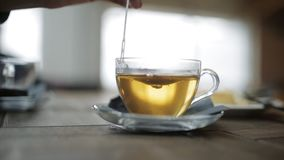 Woman`s hand stir the sugar in a Cup of tea in a cafe at the airport. Close-up of cups of tea on table in cafe stock footage
