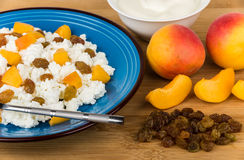 Close up of curd with peaches and raisins, sour cream Stock Image