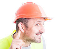 Close-up of curious young builder listening whispers Royalty Free Stock Photos