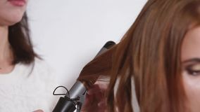 Close-up of curling iron in a hand of hairstylist, making hairdo for woman stock video footage