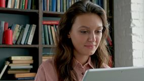 Close up of the curly young woman in glasses working on the tablet device and smiling to the camera at the library stock video
