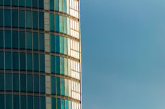 Close Up Curved Skyscraper. Side of Rounded Office Block Set Against Plain Blue Sky Royalty Free Stock Photo