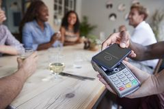 Close Up Of Customer In Restaurant Paying Bill With Contactless Phone App royalty free stock photo