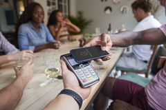 Close Up Of Customer In Restaurant Paying Bill With Contactless Phone App royalty free stock photos