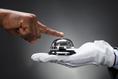 Customer Ringing Service Bell Held By Butler stock image