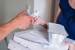 Customer`s hand giving money for to delivery man royalty free stock photo