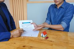 Close up of customer signing a paper document for buying house. Estate agent pointing finger showing where to sign on wooden desk royalty free stock photo