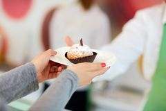 Close up of customers hand taking cupcake royalty free stock photo
