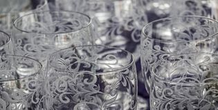Close-up of cut and cisiliated colourless drinking glasses with abstract patterns royalty free stock photos