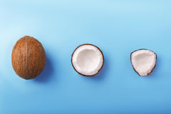 Close-up cut coconuts on a blue wooden background. Tasteful healthful cracked coco. Pieces of a beautiful white coconut. Stock Image