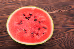 Close-up of a cut round juicy watermelon on the wooden background. The pulp of watermelon is refreshingly sweet. Royalty Free Stock Photos