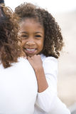 Close-up cute African-American girl in mom's arms. Close-up of cute six year old African-American girl in mother's arms Stock Photos