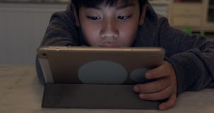 Close up of cute asian boy using tablet computer ,Young teenage boy playing games. On digital tablet with smile face stock video
