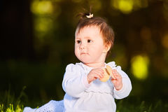 Close-up of cute baby girl sitting in the park and eats the snack at warm day. Beautiful little girl in the white dress. Summer or spring season in the city Stock Photos