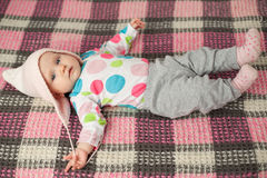 Close up cute baby in a pink hat. Cute baby girl in a pink hat on a checkered plaid Royalty Free Stock Photo