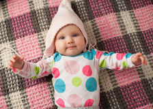 Close up cute baby in a pink hat. Cute baby girl in a pink hat on a checkered plaid Royalty Free Stock Photos