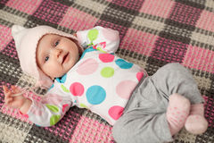 Close up cute baby in a pink hat. Cute baby smiling  and gesturing against checkered background Royalty Free Stock Photography
