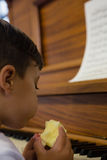 Close up of cute boy eating apple while sitting by piano Stock Photos