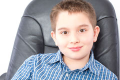 Close up Cute Boy Sitting on an Office Chair Stock Photos
