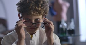 Close-up of cute Caucasian boy with curly hair taking off and putting on eyeglasses. Clever teenager looking at camera
