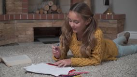 Close-up of a cute Caucasian girl coloring pictures as laying at the soft carpet. Pretty young lady resting at weekends stock footage