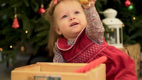 Close up for cute child girl with decorative golden ball sitting near christmass tree. Little baby girl reaching up her royalty free stock images