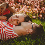 Close up of cute couple lying on green grass in park and spending time together Stock Photos